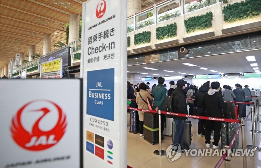 资料图片:3月8日,在首尔金浦机场,准备前往日本的乘客排起长龙等待办理乘机手续。 韩联社
