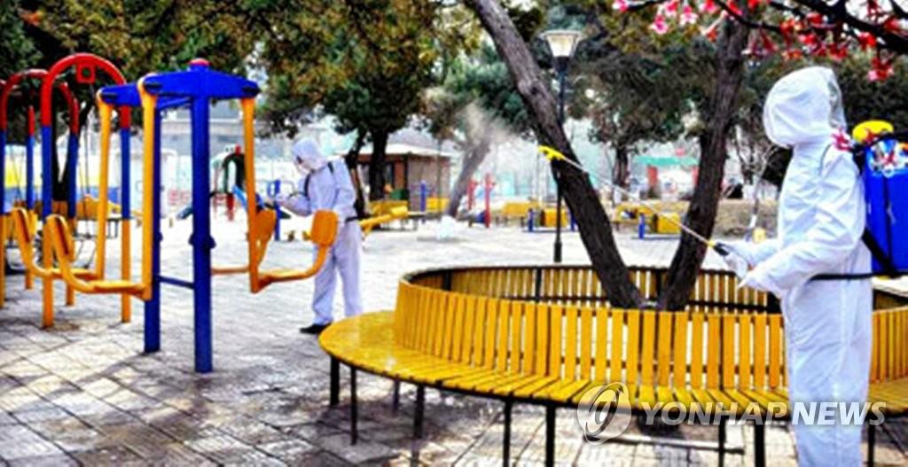 资料图片:工作人员正在公共场所进行消毒。 韩联社/《劳动新闻》官网截图(图片仅限韩国国内使用,严禁转载复制)