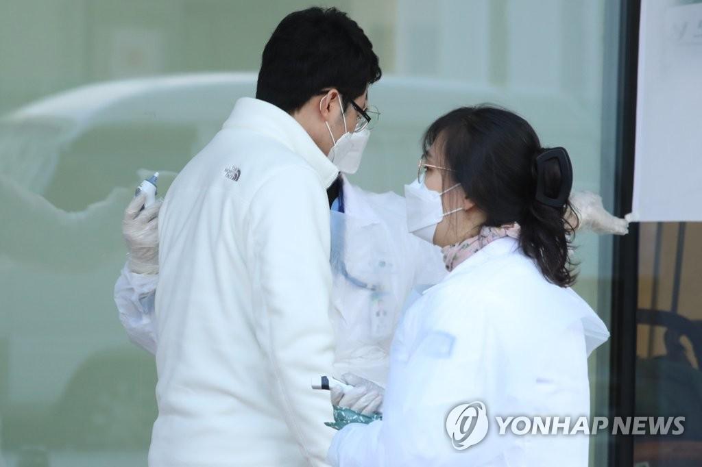 资料图片:3月9日上午,在首尔市恩平圣母医院,一位访客测量体温。该院因出现确诊病例于2月21日临时关闭,9日上午恢复门诊。 韩联社