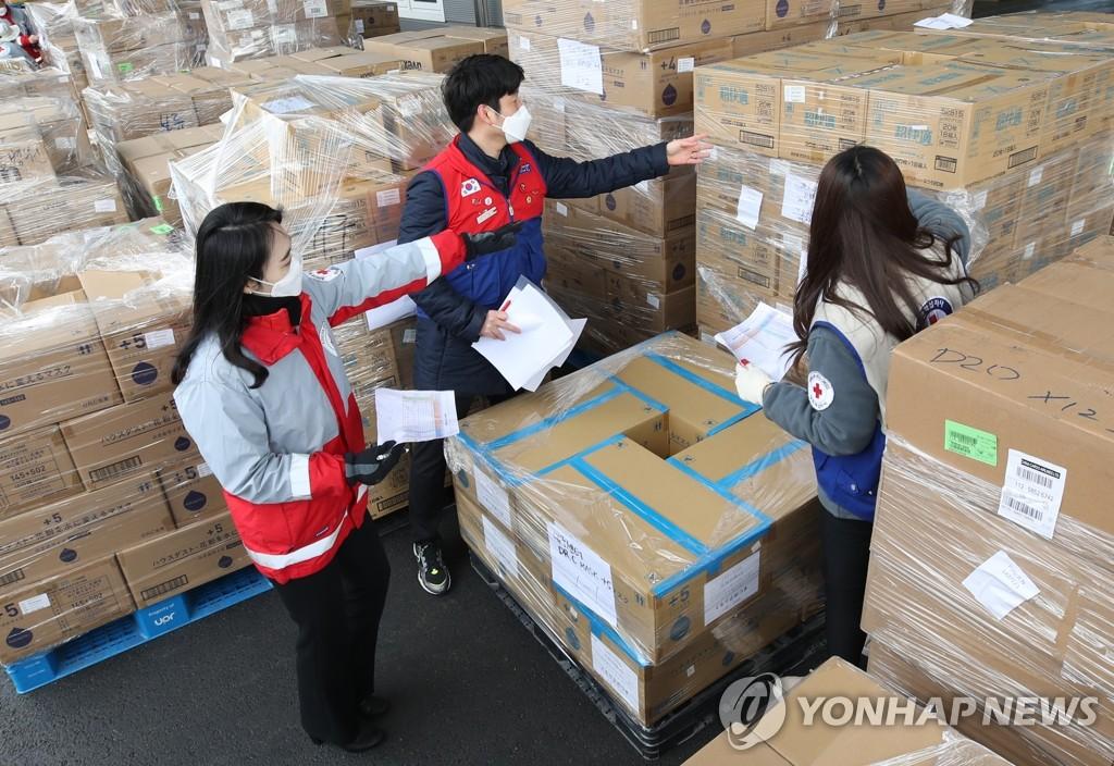 资料图片:3月12日,在仁川市中区一物流仓库,大韩红十字会的工作人员在对中国阿里巴巴集团创始人马云捐赠的100万个口罩进行物流分类,将口罩配发至全国各地。 韩联社