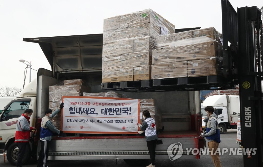 资料图片:3月12日上午,在仁川市中区一处物流仓库,大韩红十字会工作人员将马云捐赠的100万只口罩送往全国各地。 韩联社