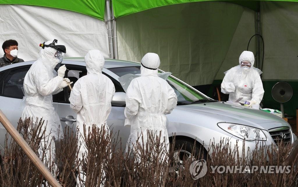 资料图片:医务人员实施免下车筛查。 韩联社
