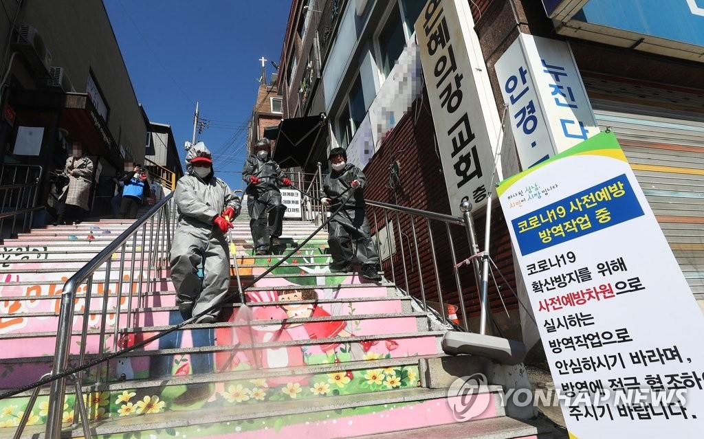 资料图片:3月16日,在京畿道城南市寿井区,防疫人员进行消毒防疫。 韩联社