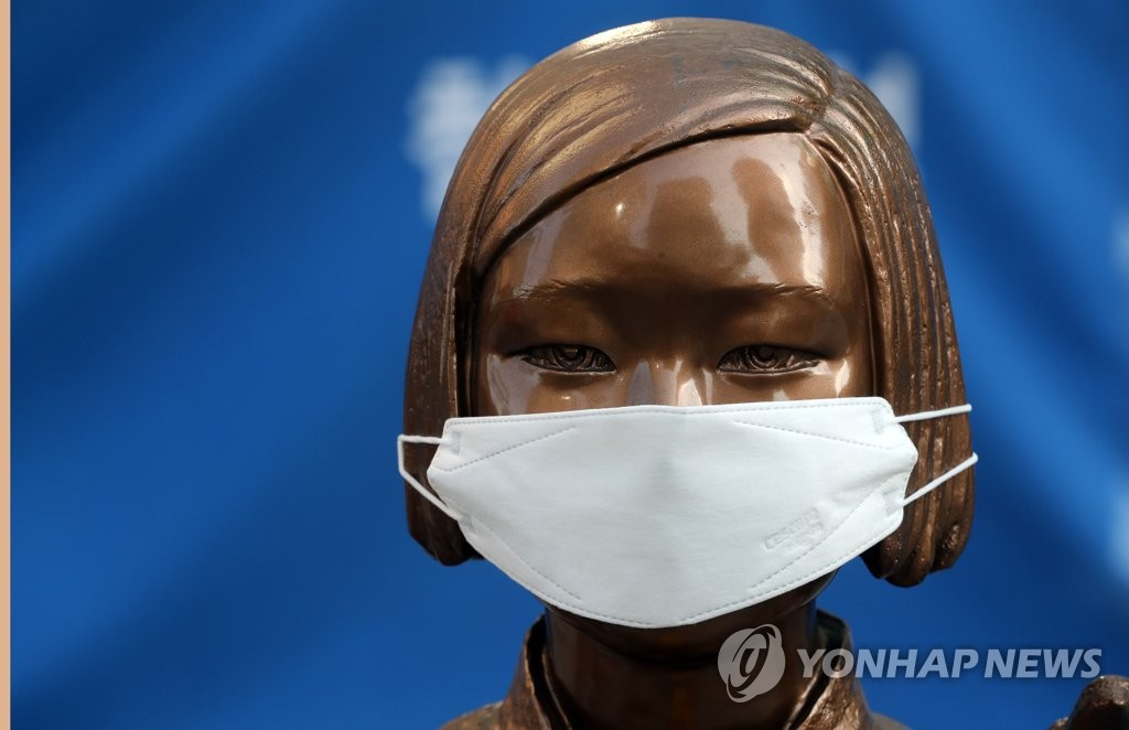 """资料图片:3月18日,在首尔光化门日本驻韩国大使馆旧址前,第1431次""""周三集会""""受疫情影响改为网上直播的形式进行,纪念慰安妇受害者的""""和平少女像""""也戴上了口罩。 韩联社"""