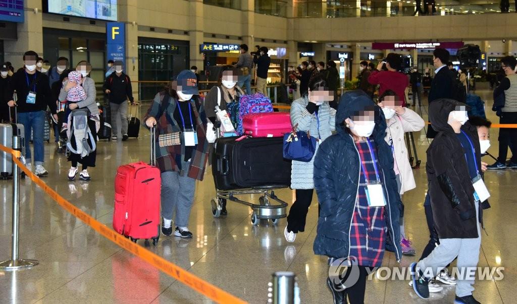 资料图片:3月19日,乘坐政府安排的包机从伊朗撤回的侨民抵达仁川国际机场。 韩联社