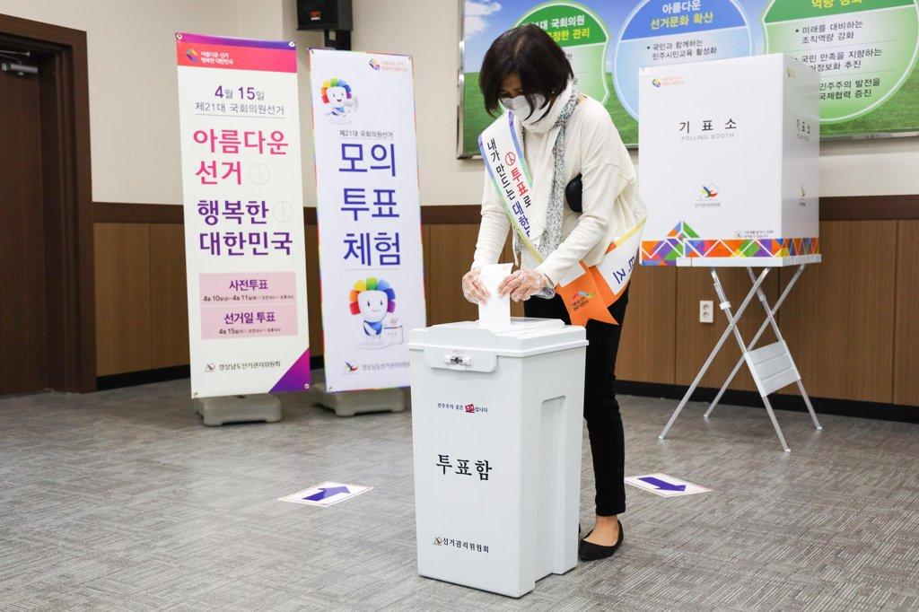 资料图片:3月25日,在庆尚南道选举管理委员会大会议室,戴着口罩、手套的工作人员体验国会议员选举模拟投票。 韩联社/庆南选委会供图(图片严禁转载复制)