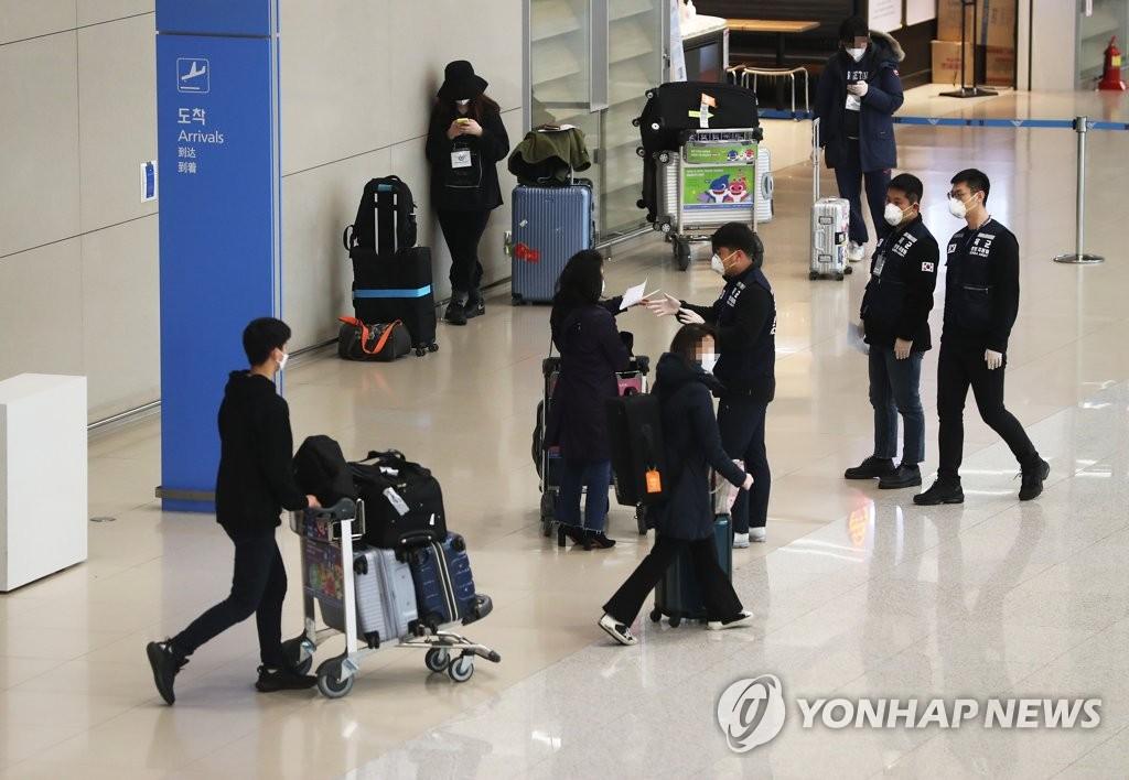 资料图片:3月25日,在仁川国际机场第二航站楼入境厅,防疫人员向自欧入境者介绍检疫流程。 韩联社