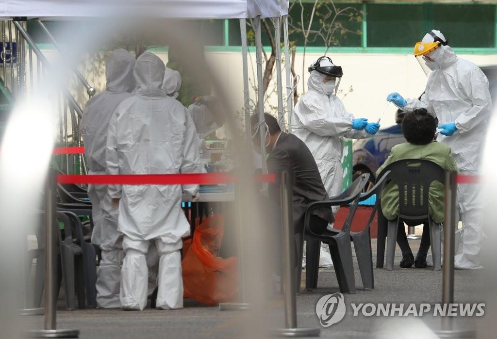 资料图片:3月28日,在首尔九老区万民中央教会前,该教会教徒在临时筛查诊所接受新冠病毒检测。 韩联社