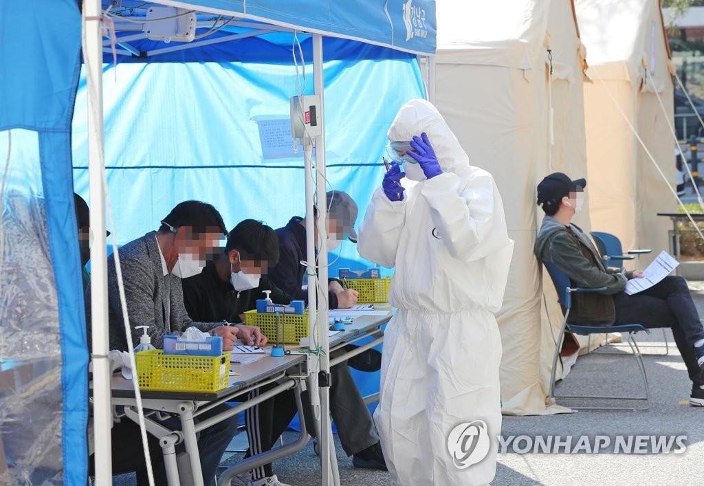 资料图片:在筛查诊所填表的市民们 韩联社