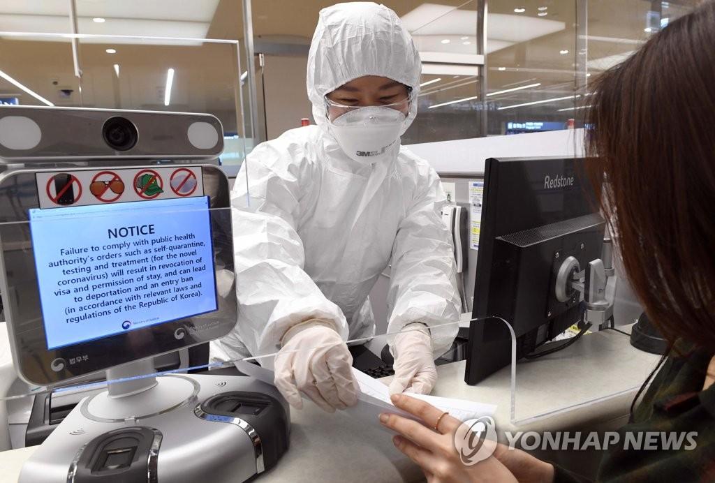 4月8日下午,在仁川机场,边检人员向有症状入境旅客说明居家隔离须知。 韩联社