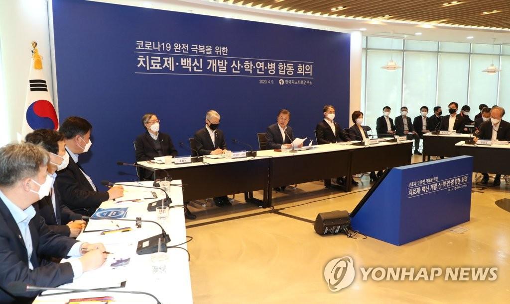 4月9日,文在寅(中间)出席新冠疫情科研会议。 韩联社