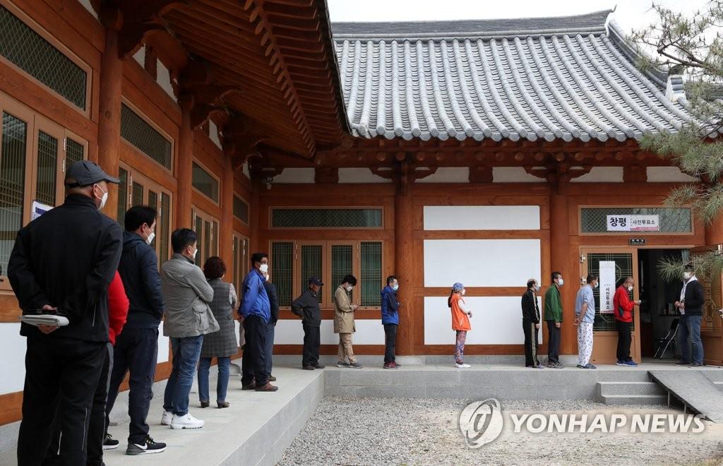 4月10日,在全罗南道潭阳郡昌平面事务所,戴着口罩排队投票的选民保持社交距离。 韩联社