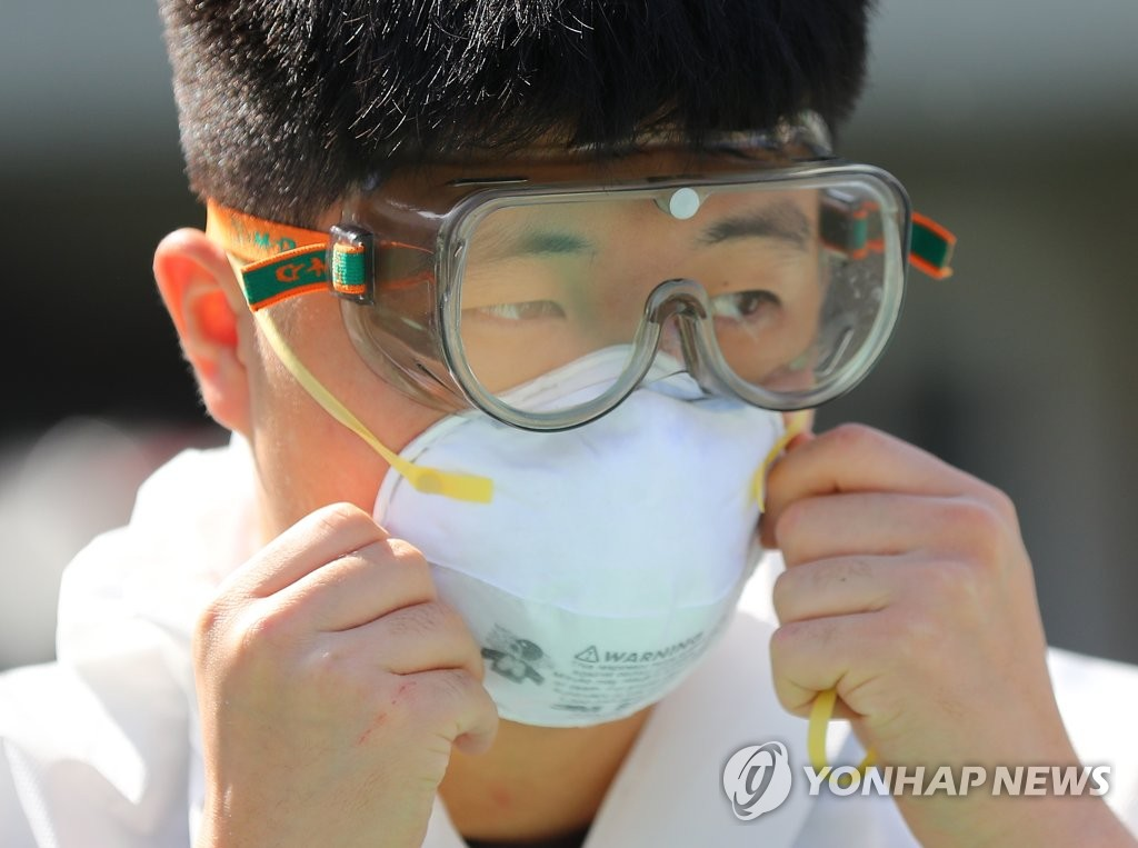 资料图片:4月14日,在大邱南区庆北艺术高中,一名陆军士兵戴防护镜和口罩防疫。 韩联社