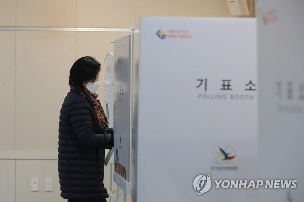 资料图片:4月15日,在光州南区的一投票站,一位选民戴着口罩进入划票间。 韩联社