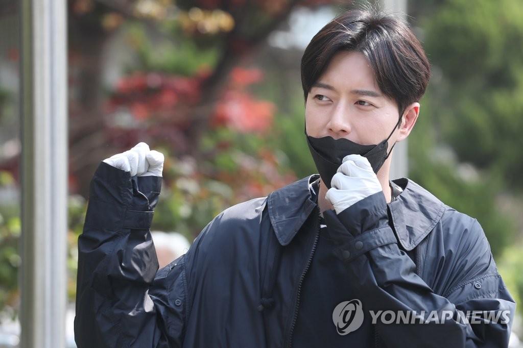 4月15日,在首尔瑞草区的一处投票站,演员朴海镇举手致意。 韩联社