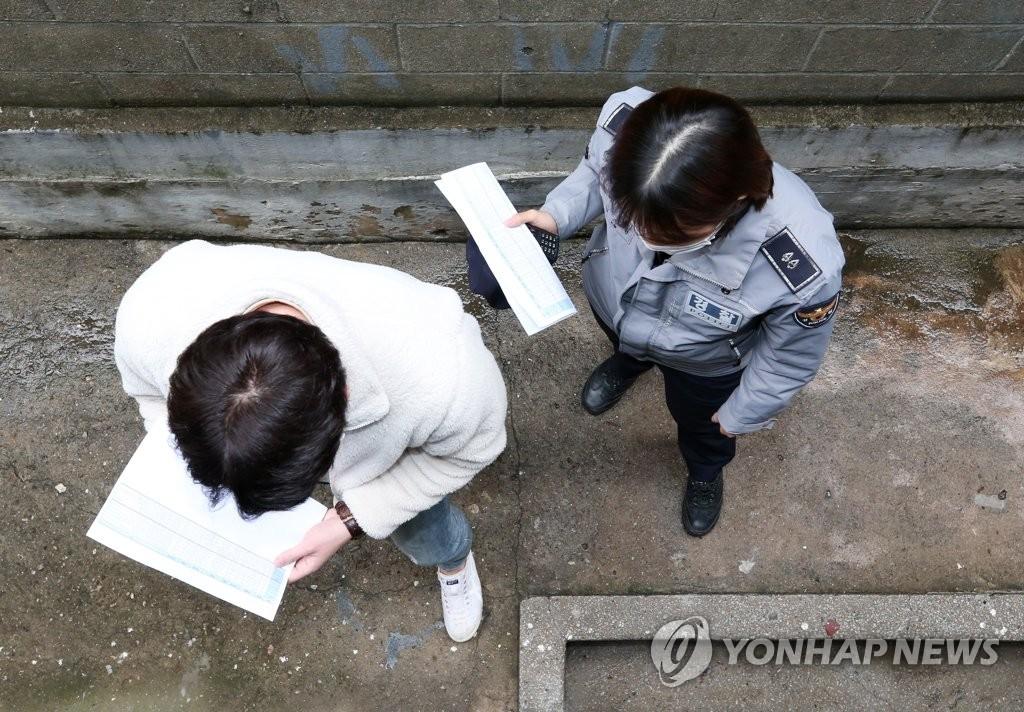 资料图片:4月17日,在仁川市,新冠应对检查组工作人员突击访问居家隔离人员的居所。 韩联社