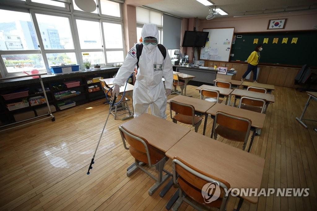 资料图片:4月21日,在大邱市中区明德小学,一名陆军士兵为教室消毒。 韩联社