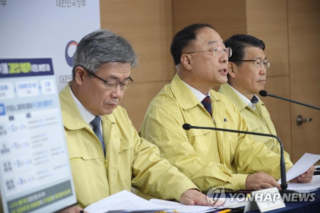 4月22日,在政府首尔大楼,韩国副总理兼企划财政部长官洪楠基(居中)出席第五次紧急经济会议联合记者会。 韩联社