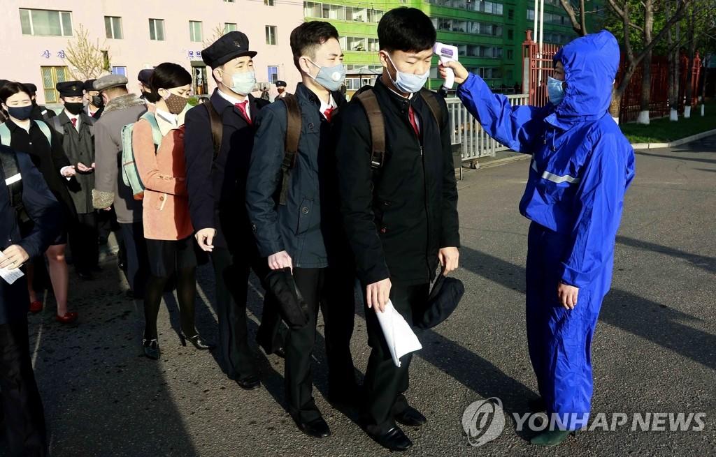资料图片:4月22日,在位于朝鲜平壤市的金策工业大学,学生们在校门前接受测温。 韩联社/美联社(图片严禁转载复制)
