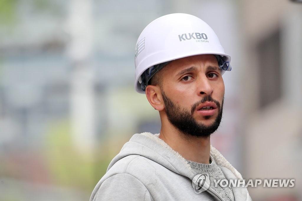 资料图片:在首尔中区施工现场工作的一名外籍劳动者 韩联社