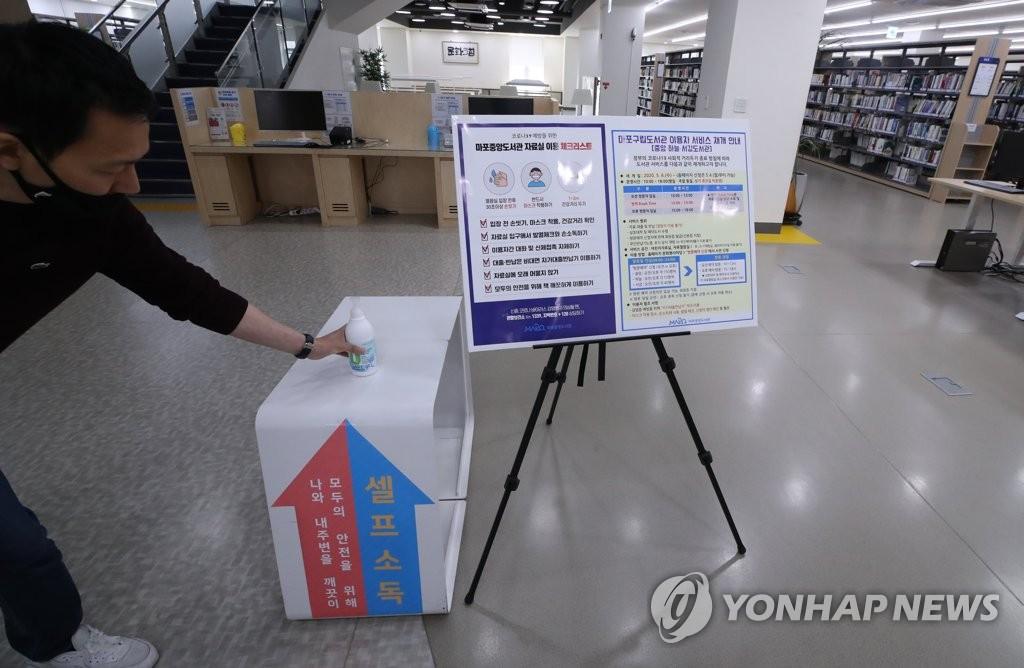 资料图片:5月4日,在首尔麻浦中央图书馆,工作人员准备手消毒液。 韩联社