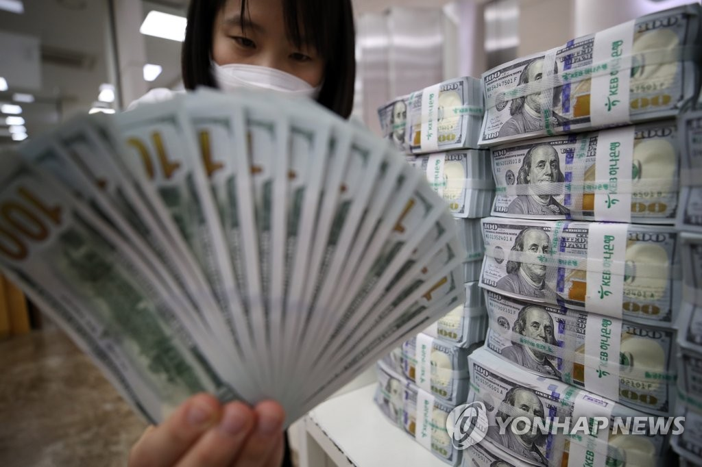 资料图片:5月6日,在位于首尔中区的韩亚银行总部,工作人员在清点美元。 韩联社