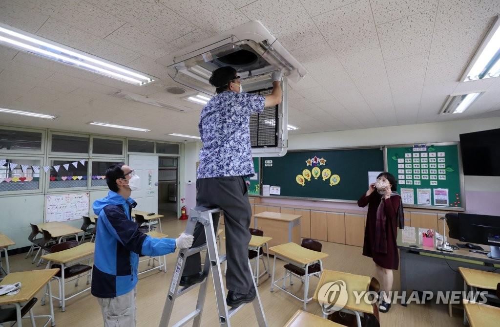 5月7日,在首尔市一所小学,校长和教职工进行空调清洗维护工作。教育部规定打开教室三分之一以上的窗户才能使用空调以免密闭空间传染病毒。 韩联社