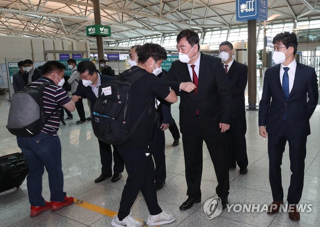 """5月10日,在仁川国际机场,中国驻韩国大使邢海明(右二)为利用""""快捷通道""""制度前往中国天津的三星显示器员工送行。 韩联社"""