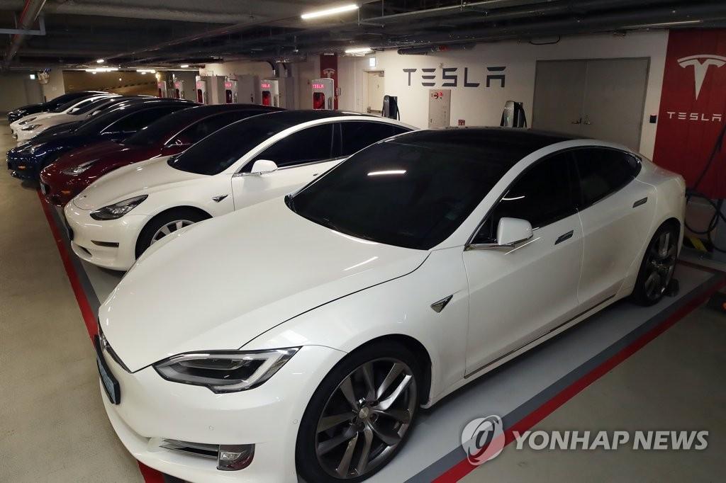 资料图片:特斯拉电动汽车在充电站充电。 韩联社