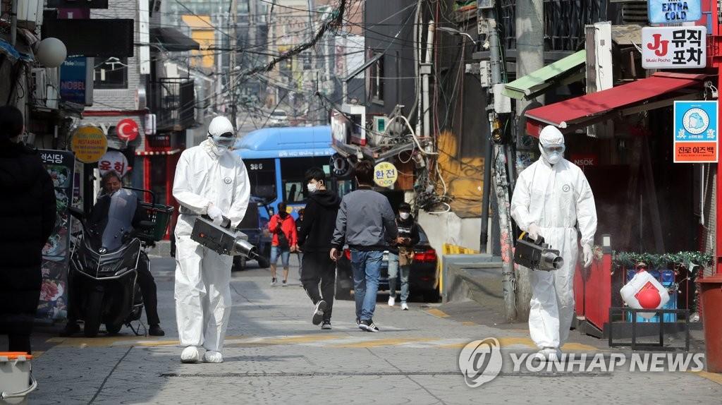 资料图片:5月11日上午,在首尔市梨泰院酒吧街,龙山区卫生站的工作人员在街头进行消毒防疫。 韩联社