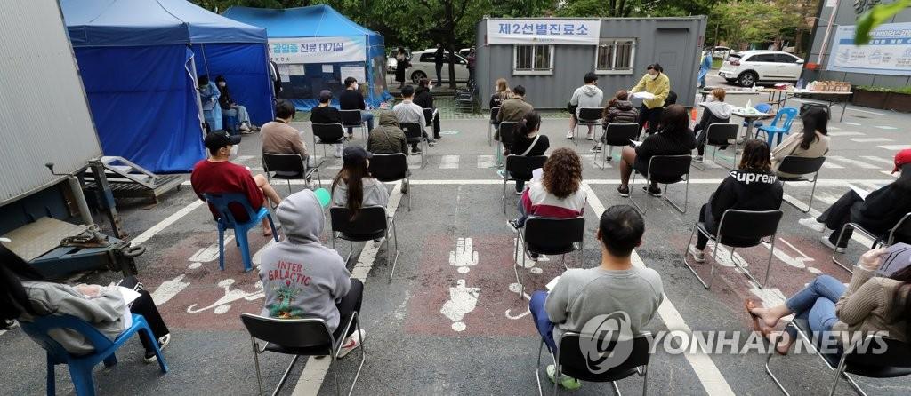 资料图片:5月12日,在首尔城东区卫生站外的一处开放型筛查站,人们排长队等候接受新冠病毒检测。 韩联社