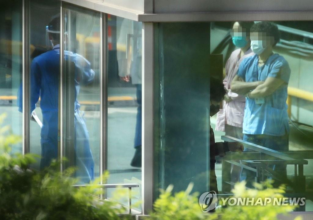 资料图片:5月20日,在首尔市江南区三星首尔医院停车场,医护人员准备接受病毒检测。 韩联社