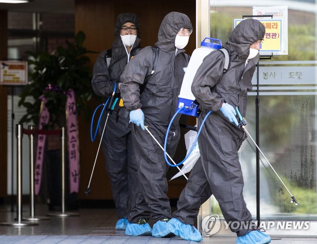 工作人员在仁川仁港高中进行消毒防疫。 韩联社