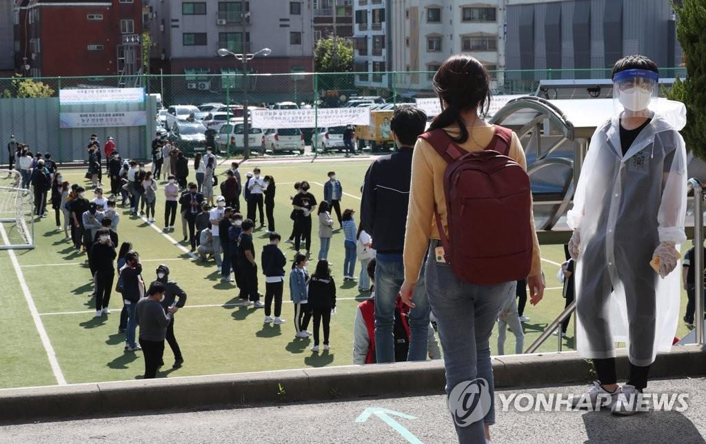 资料图片:5月20日,在仁川市弥邹忽区的筛查诊所,市民等待接受检测。 韩联社
