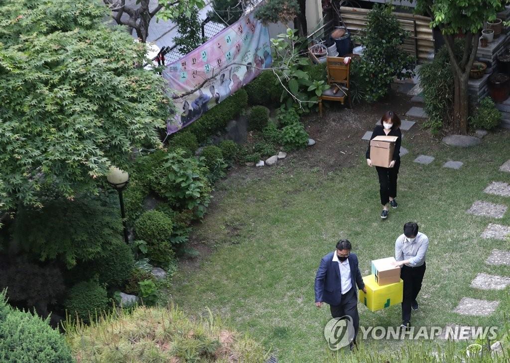 """资料图片:5月21日,韩国检方对位于首尔市麻浦区的慰安妇养老院""""我们的和平之家""""进行搜查取证。图为检方工作人员结束搜查取证后搬出相关资料。 韩联社"""