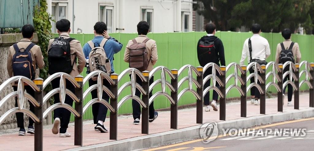 资料图片:5月25日,在仁川市弥邹忽区的一所高中前,学生们走在上学路上。韩国高三学生20日返校复课,当天有2名学生确诊感染新冠病毒,受此影响,仁川地区66所学校的高三学生线下复课推迟到25日。 韩联社