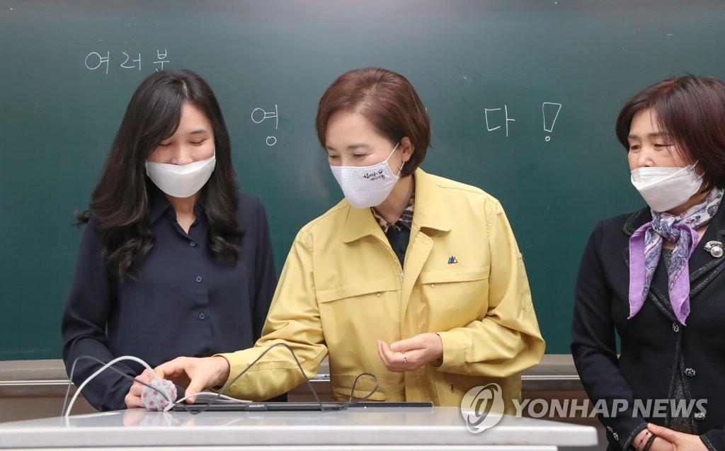 资料图片:5月25日上午,在首尔龙山区的一所中学,韩国副总理兼教育部长官俞银惠(中)与教师们交谈。在初中生、小学生等也即将返校复课之际,俞银惠视察该校,检查防疫工作。 韩联社