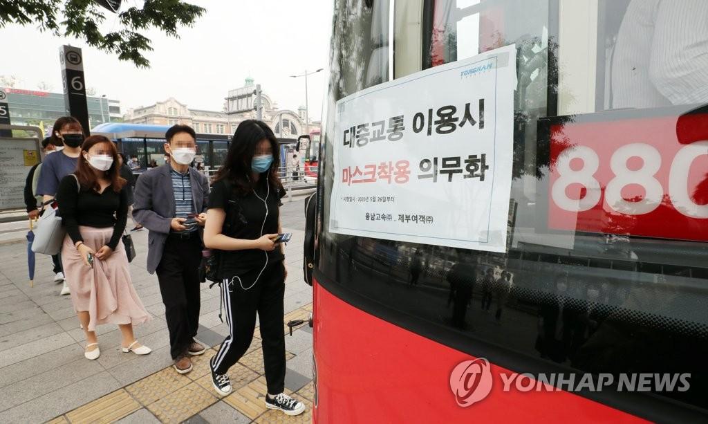 资料图片:5月26日上午,在首尔站换乘枢纽站,市民们戴着口罩坐公交车。 韩联社