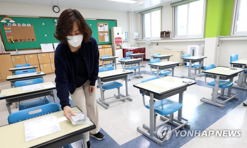 资料图片:5月26日,在江原道春川市一所小学,教师把口罩放在课桌上。 韩联社