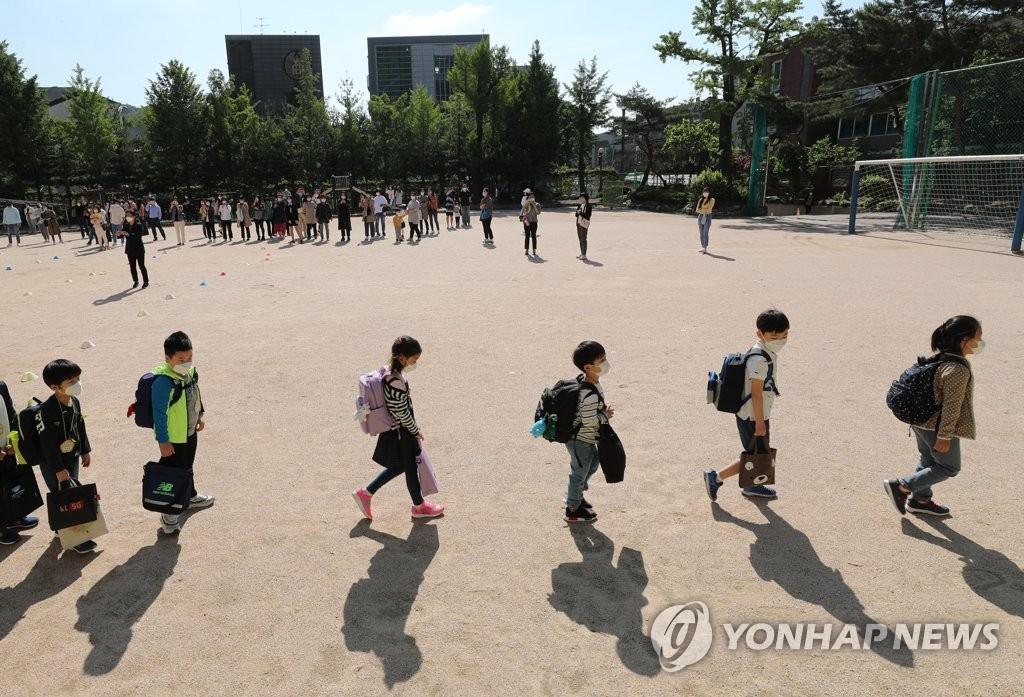 资料图片:5月27日上午,首尔钟路区一所小学,新生们结束入学仪式后,保持距离走回教室。 韩联社