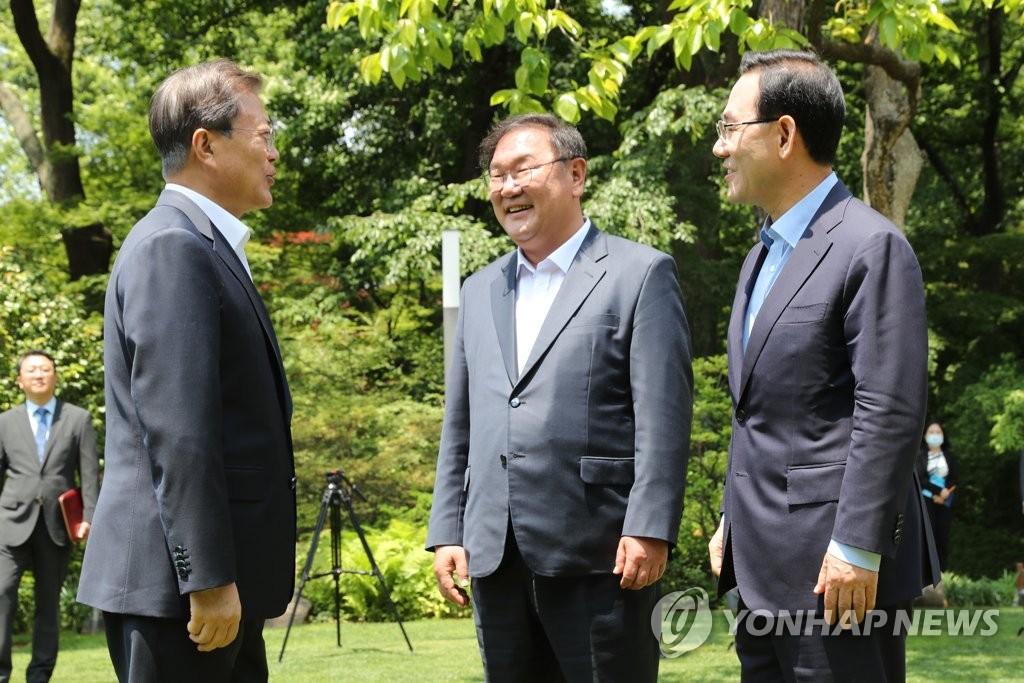 5月28日,在青瓦台,韩国总统文在寅(左)与执政党共同民主党党鞭金太年(中)、最大在野党未来统合党党鞭朱豪英交谈。 韩联社