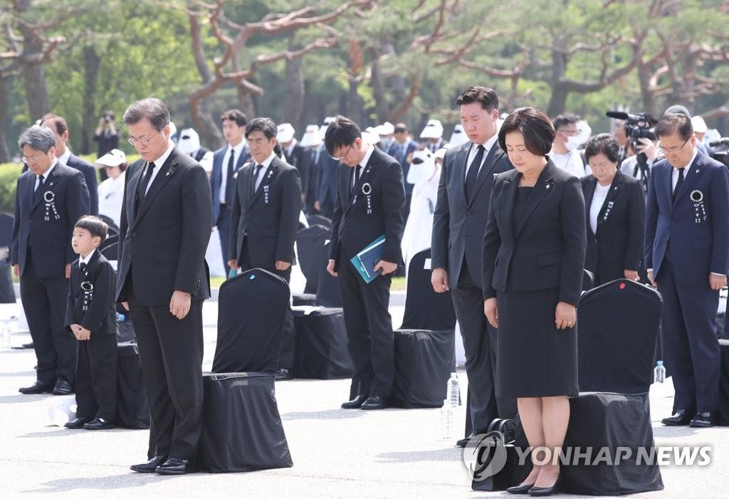 6月6日上午,文在寅(左)和夫人金正淑女士在第65届显忠日纪仪式上默哀。韩联社