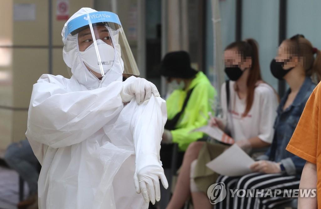 资料图片:医疗人员穿着防护服准备进行病毒检测。 韩联社