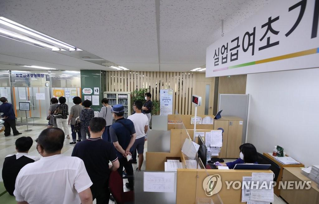 资料图片:大批待业者排队进入位于首尔中区的就业福利中心,准备听取失业津贴领取说明。 韩联社