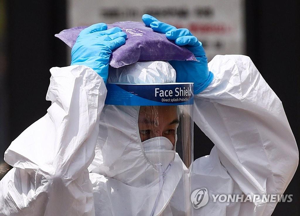 资料图片:6月11日,在首尔市阳川区卫生站筛查诊所,一名医务人员身穿防护服,头顶冰袋消暑。首尔市当天骄阳似火,最高气温超过30摄氏度。 韩联社