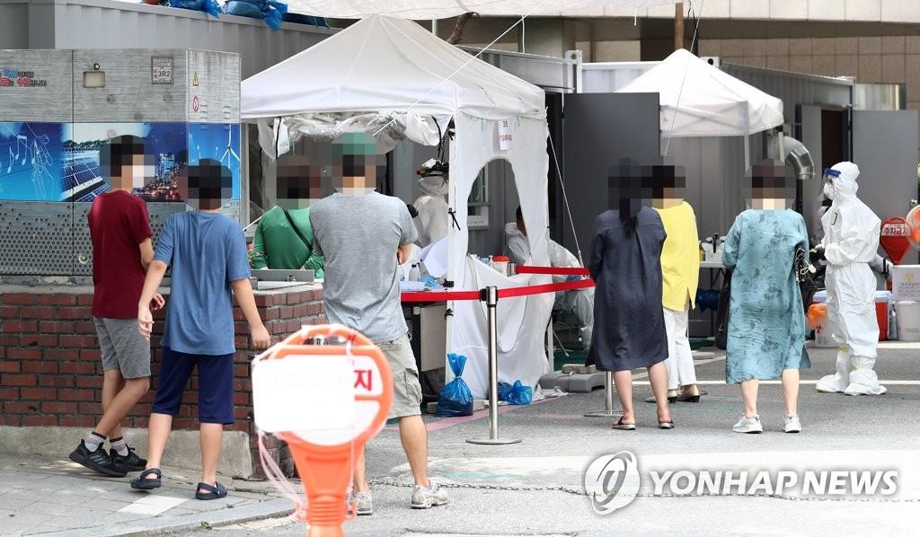 资料图片:6月17日上午,在位于大田市的一所筛查诊所,市民排队候检。 韩联社