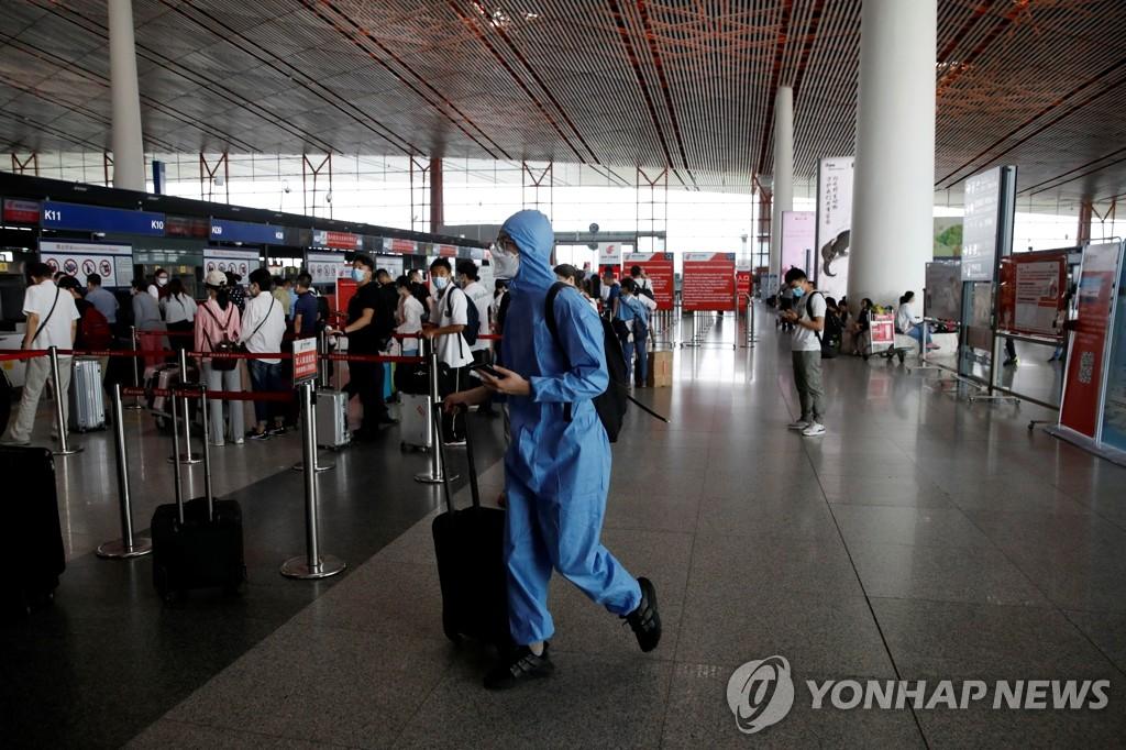 资料图片:6月17日,一名旅客穿着防护服走在北京首都机场国际出发候机厅。 韩联社/路透社(图片严禁转载复制)