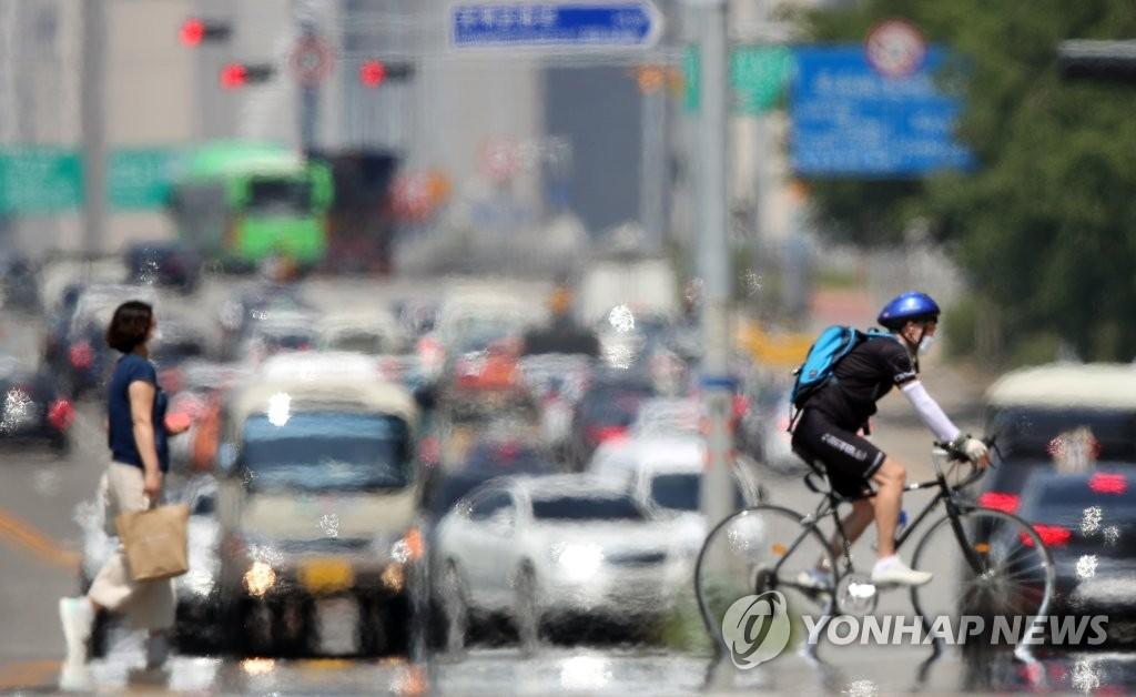 资料图片:6月22日下午,在首尔永登浦区汝矣岛一带,天气炎热,路面热气升腾。首尔当天最高气温达35摄氏度。 韩联社