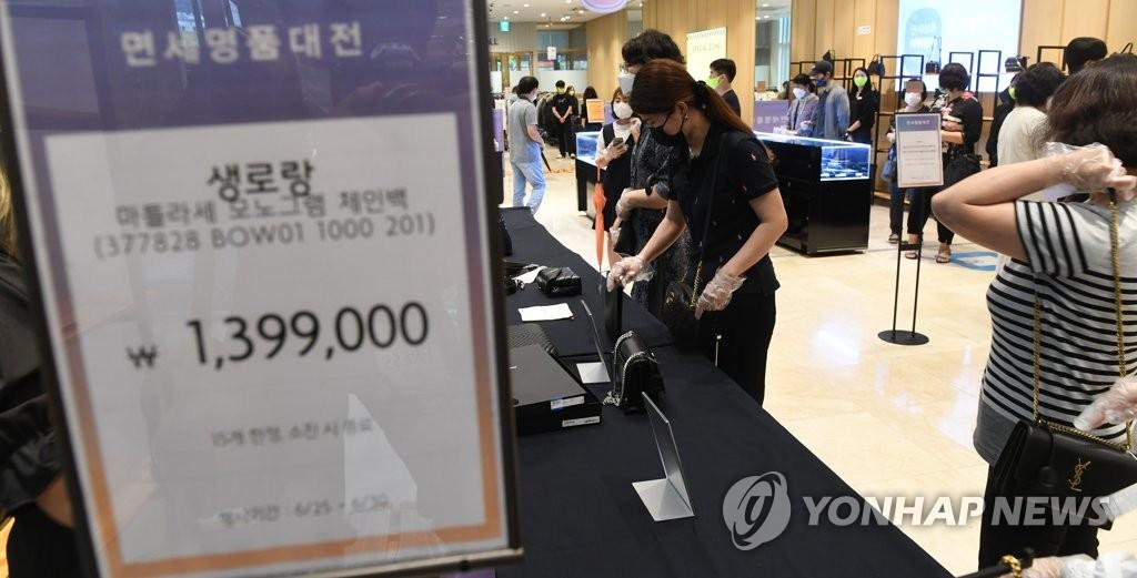 6月25日上午,消费者们在乐天百货芦原店购买库存。 韩联社