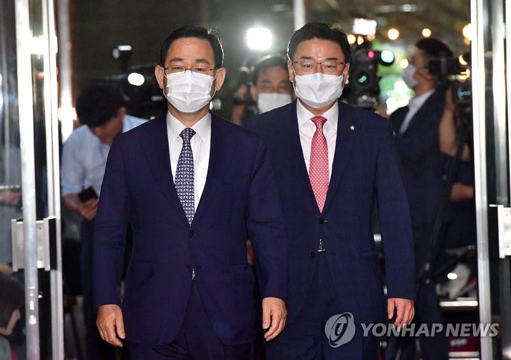 6月29日,统合党党鞭(左)朱英豪和国会首席副代表金成愿进入国会准备与执政党就成立常任委员会进行磋商。 韩联社